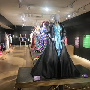 Main exhibit room for In Her Closet featuring drag costumes on grey mannequins. Text descriptions printed on multiple colored posters along black walls.